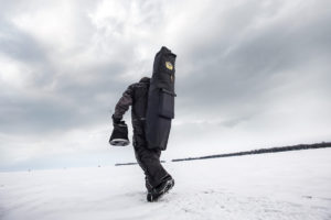 "Brian ""Bro"" Brosdahl carrying a hub ice shelter to his ice fishing spot"